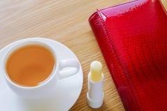 Su una tavola un la tazza di tè, di rossetto e di una borsa Immagine Stock Libera da Diritti