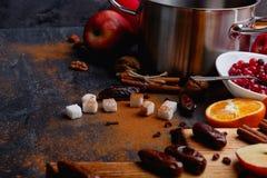 Su una tavola, zucchero, cannella, una casseruola, un piatto con i mirtilli rossi, un bordo con le date Vista laterale Fine in su immagine stock