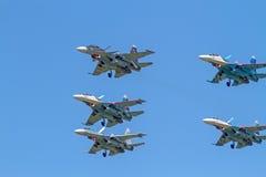 Su-30 und vier Su-27 im blauen Himmel Stockfotografie