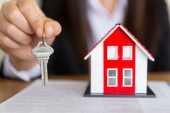 Sua casa nova, chave da casa da terra arrendada do mediador imobili?rio a seu cliente ap?s ter assinado o acordo de contrato no e fotos de stock