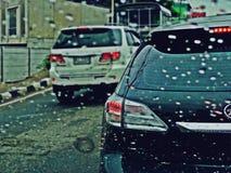 Suan Luang,泰国- 2018年11月10日:交通在路和雨下落的下雨天在与跟踪断裂光的车窗 免版税库存照片
