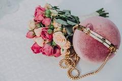 Suavemente embrague rosado redondo y ramo nupcial de rosas blancas y rosadas en un fondo blanco foto de archivo