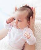 Suavemente manos de la madre que detienen al bebé Recién nacido regordete y hermoso foto de archivo