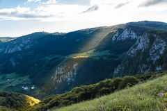 Sub piatra. Monastery, revealed by a sun light through the clouds Stock Photo
