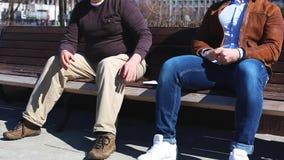 Sub?rnos de transfer?ncia na rua Um homem d? o dinheiro em um envelope a um outro homem ao sentar-se no banco no parque vídeos de arquivo