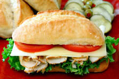 Sub Sandwich. Turkey, lettuce, cheese and tomatoes fill a sub roll making an appetizing sandwich.  Condiments and fresh bread in the background Royalty Free Stock Photography