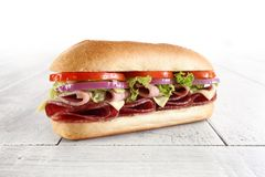 Sub sandwich on white table. Sub sandwich with meat and vegetables on white table Stock Photos