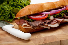 A sub sandwich on a wooden cutting board Royalty Free Stock Photography
