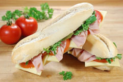 Sub sandwiches. Sub sandwich baguettes with ham and cheese on a chopping board Stock Photography