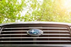Subaru emblem på ett elementgaller mot grön lövverk och med solljus till rätten royaltyfria foton