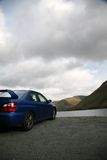 Subaru Impreza by the Lake in the Mountains. Picture GT Vehicle in the Mountains - Concept of Long Journey and Traveling by Car - Moody Weather in the Mountains royalty free stock photos