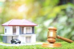 Subasta de la propiedad, casa de madera y modelo del mazo en fondo verde natural, abogado de las propiedades inmobiliarias casera fotos de archivo libres de regalías
