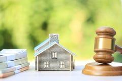 Subasta de la propiedad, casa de madera y modelo del mazo en fondo verde natural, abogado de las propiedades inmobiliarias casera fotos de archivo