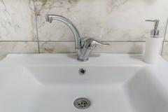 Säubern Sie modernen Badezimmerchromhahn Stockbilder