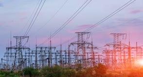 Subestação elétrica da distribuição com linhas elétricas e transformadores, no por do sol fotos de stock
