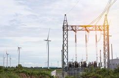 Subestación de alto voltaje del pilón de la corriente eléctrica con energía eólica renovable de las turbinas de viento imagenes de archivo