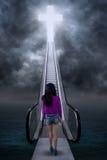 Subida adolescente de la muchacha una escalera a la cruz Fotos de archivo