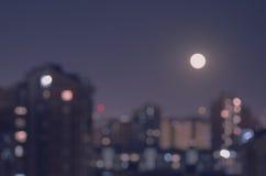 Subida de la luna de Defocusl sobre ciudad en la noche Imagen de archivo libre de regalías