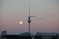 Subida de la luna detrás de la torre Alexanderplatz de T.V Fotografía de archivo