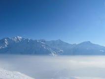 Subida de los picos de montaña sobre las nubes Imagenes de archivo