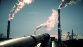 Subida de los tubos y del humo de la red de la distribución del calor de la chimenea grande en el cielo azul Tiro est?tico almacen de metraje de vídeo