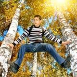 Subida del adolescente un árbol Foto de archivo libre de regalías