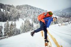 Subida del invierno al top de la montaña con una mochila Imágenes de archivo libres de regalías