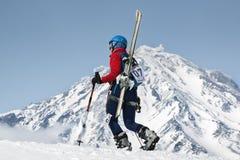 Subida del montañés del esquí de la muchacha en la montaña en el volcán del fondo Fotos de archivo libres de regalías