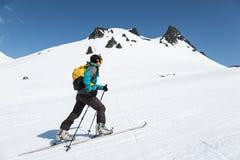 Subida del montañés del esquí en los esquís en la montaña Fotografía de archivo