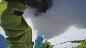 Subida del Snowboarder en la montaña nevosa superior para el paseo backcountry asoleado peligroso almacen de video