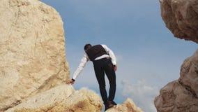 Subida elegante joven del hombre en las monta?as muy cuidadosamente con sus pasos chipre Paphos almacen de metraje de vídeo