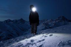 Subida turística profesional en la montaña nevosa en la noche y las luces la manera con un faro Snowboarder que camina delante de Imagenes de archivo