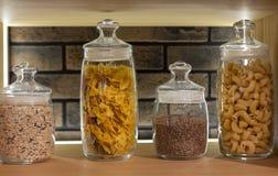 Subida y guisantes de las pastas en un estante en un tarro de cristal en un interior moderno foto de archivo libre de regalías