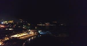subidas aéreas de 4K UHD sobre la ciudad de la noche cerca del mar que pasa por alto la tempestad de truenos, relámpago almacen de metraje de vídeo