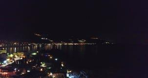 subidas aéreas de 4K UHD sobre la ciudad de la noche cerca del mar que pasa por alto la tempestad de truenos, relámpago almacen de video