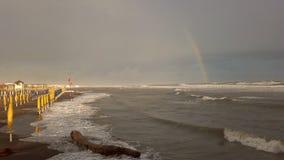 Subidas de las aguas abajo en las costas con el mar agitado y el arco iris hermoso almacen de metraje de vídeo