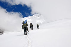 Subir a tres escaladores en Titnuld Foto de archivo