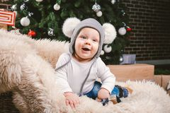 Subject children christmas new year. Caucasian little funny baby boy 1 year old sitting sleigh bear skin Christmas tree head warm. Hat with balabons balls stock photos