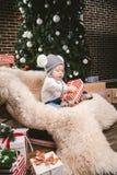 Subject children christmas new year. Caucasian little funny baby boy 1 year old sitting sleigh bear skin Christmas tree head warm stock image