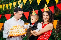 Subject children`s birthday party, food and sweets. A young family celebrates one year of son. Dad is holding a big cake, mom is royalty free stock photography