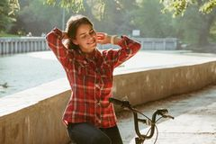 Subject ecological bicycle transport. Young caucasian woman on a dirt road in a park near a lake renting an orange-colored bike royalty free stock image