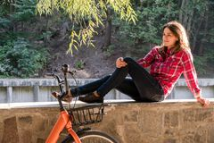 Subject ecological bicycle transport. A young caucasian woman in jeans and a shirt student sits resting in a park near the lake stock photos