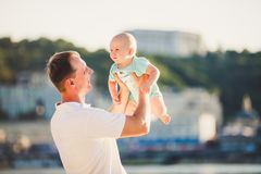 Subject Parenting, summer vacations, father and little son. Young Caucasian dad holds on arms, hugs child overlooking town Kiev. And the river on banks of stock photo