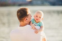 Subject Parenting, summer vacations, father and little son. Young Caucasian dad holds on arms, hugs child overlooking town Kiev. And the river on banks of stock image