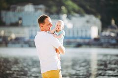 Subject Parenting, summer vacations, father and little son. Young Caucasian dad holds on arms, hugs child overlooking town Kiev. And the river on banks of royalty free stock image