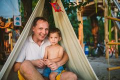 Subject Parenting, summer vacations, father and little son. Young Caucasian dad plays with child on playground in yard. Daddy and. The kid in tent teepee wigwam stock images