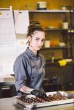 Subject profession and cooking pastry. young Caucasian woman with tattoo of pastry chef in kitchen of restaurant preparing round royalty free stock photo
