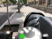 Subjective view on a camera lens taking pictures in the street Stock Images