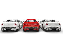 Sublime red sport car in the middle of two white cars Royalty Free Stock Photos