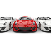 Sublime red sport car in the middle of two white cars Royalty Free Stock Photography